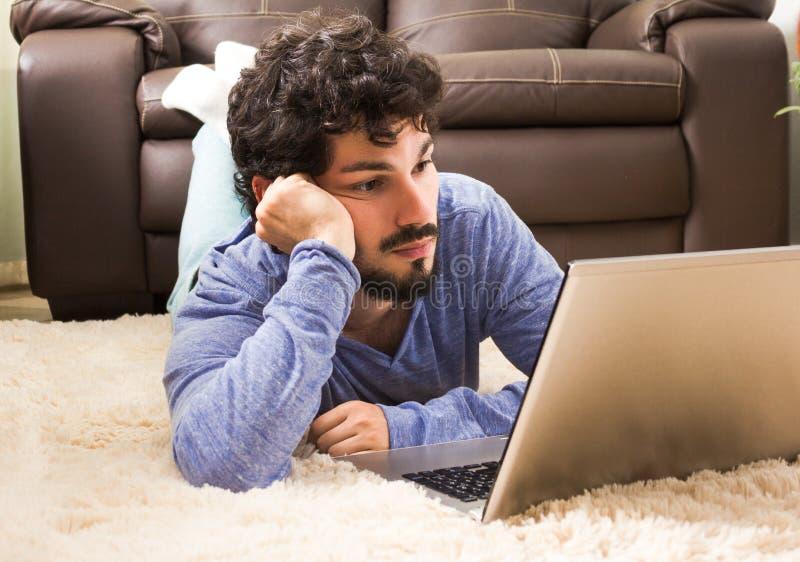 Ufficio di rapporti della lettura del lavoratore a casa Trovandosi in tappeto del tessuto felpato fotografie stock
