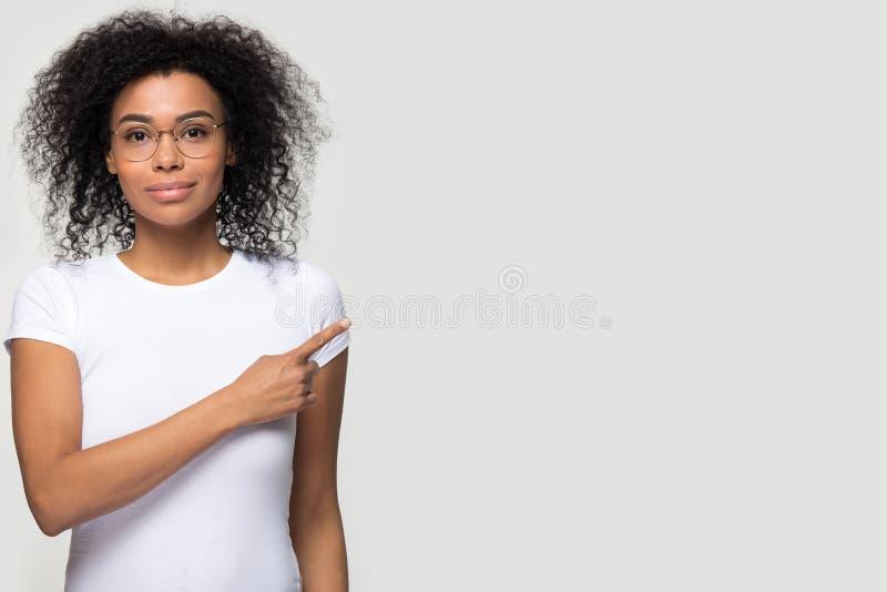 Ufna afryka?ska kobieta patrzeje kamer? wskazuje na boku w szk?ach zdjęcie stock