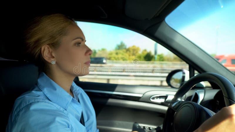Ufna biznesowa kobieta jedzie jej luksusowego samochód, utrzymuje zamkniętego oko na drodze fotografia stock