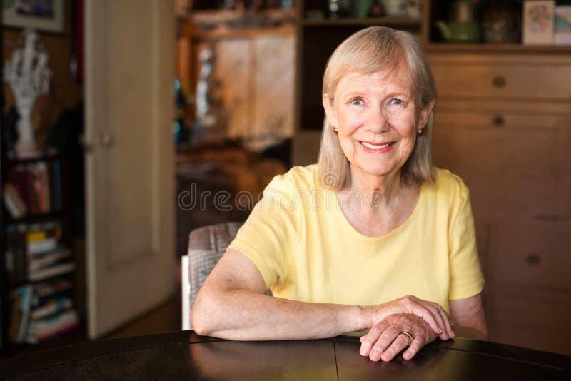 Ufna dojrzała kobieta sadzająca przy stołem obrazy royalty free