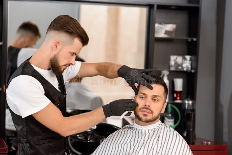 Ufna fryzjera męskiego golenia klienta ` s broda z ostrą żyletką obrazy royalty free