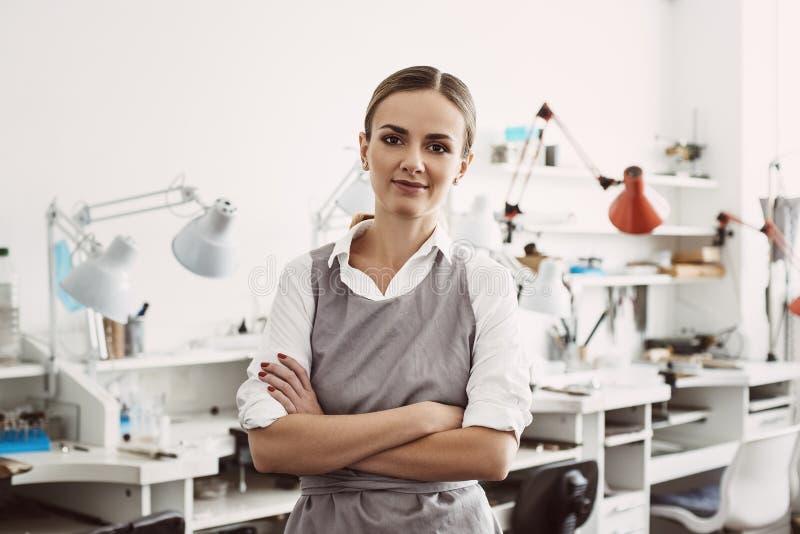 Ufna i młoda biznesowa kobieta Portret uśmiechnięty żeński jubiler w fartuch pozycji przy jej biżuteria warsztatem obraz stock