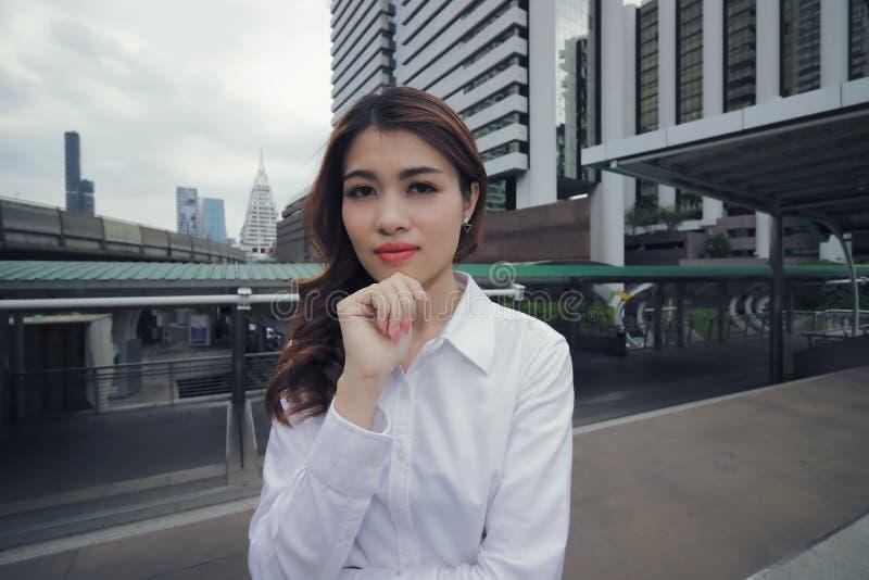 Ufna młoda Azjatycka kobiety pozycja, główkowanie pozuje przy miastowym budynku społeczeństwa tłem i zdjęcie stock
