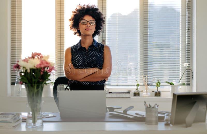 Ufna młoda bizneswoman pozycja przy jej biurkiem fotografia stock