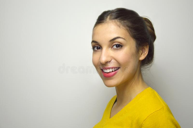 Ufna młoda kobieta patrzeje kamerę z copyspace na szarym tle z perfect uśmiechem zdjęcie royalty free