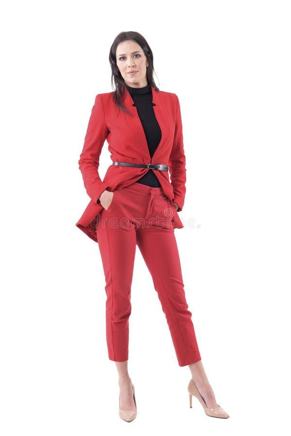 Ufna niezależna pomyślna biznesowa kobieta w czerwonym kostiumu z rękami w kieszeniach obraz stock