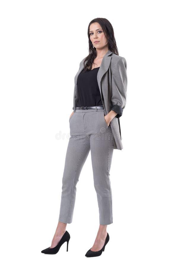 Ufna pomyślna niezależna młoda biznesowa kobieta w kostiumu z rękami w kieszeniach zdjęcia royalty free