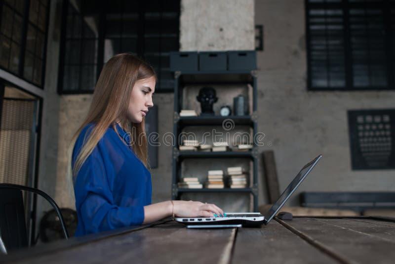 Ufna skoncentrowana młoda kobieta pracuje na laptopie podczas gdy siedzący w kreatywnie restauraci zdjęcia stock