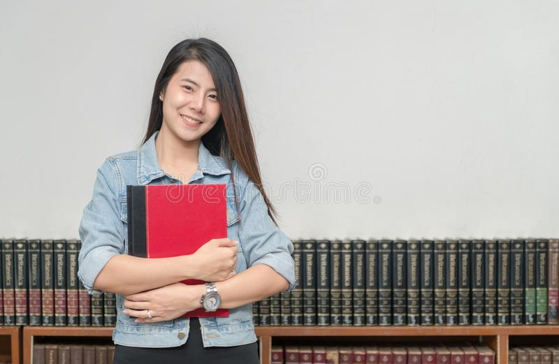 Ufna uśmiechnięta studencka azjatykcia dziewczyna w bibliotecznym uniwersytecie obrazy royalty free