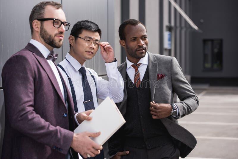 Ufna wielokulturowa biznes drużyna stoi blisko biurowego i patrzeje na boku zdjęcia royalty free