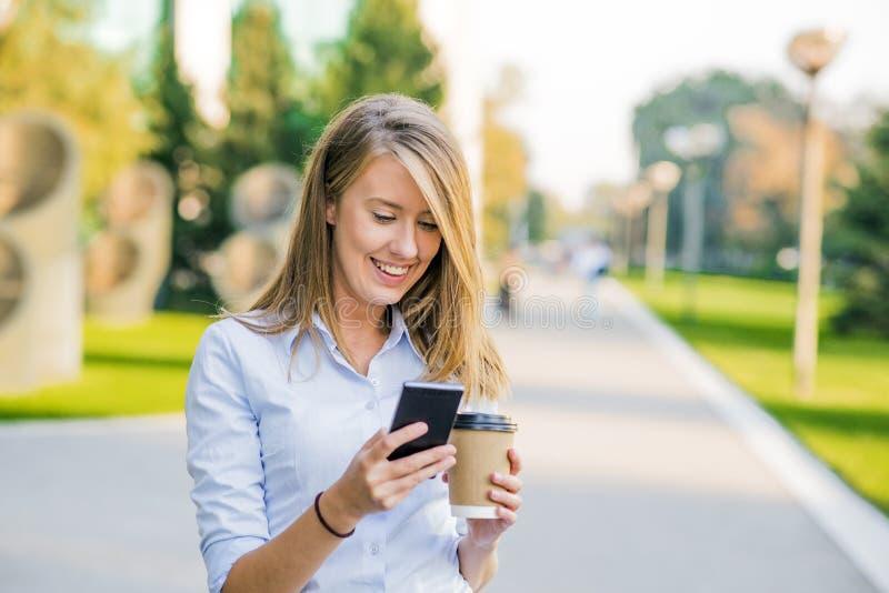 Ufne kobiety czyta informację o finansowej wiadomości podczas gdy chodzący w firma korytarzu podczas pracy przerwy zdjęcia stock