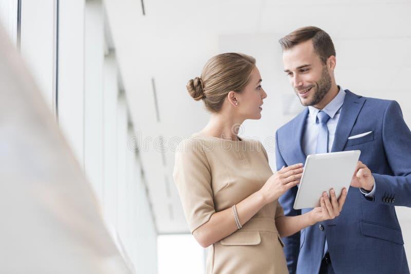Ufni młodzi biznesowi koledzy dyskutuje nad cyfrową pastylką przy nowym biurem zdjęcie royalty free