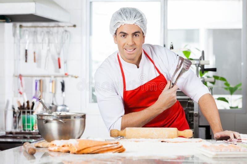 Ufni szefa kuchni mienia Tongs Podczas gdy Przygotowywający obraz royalty free