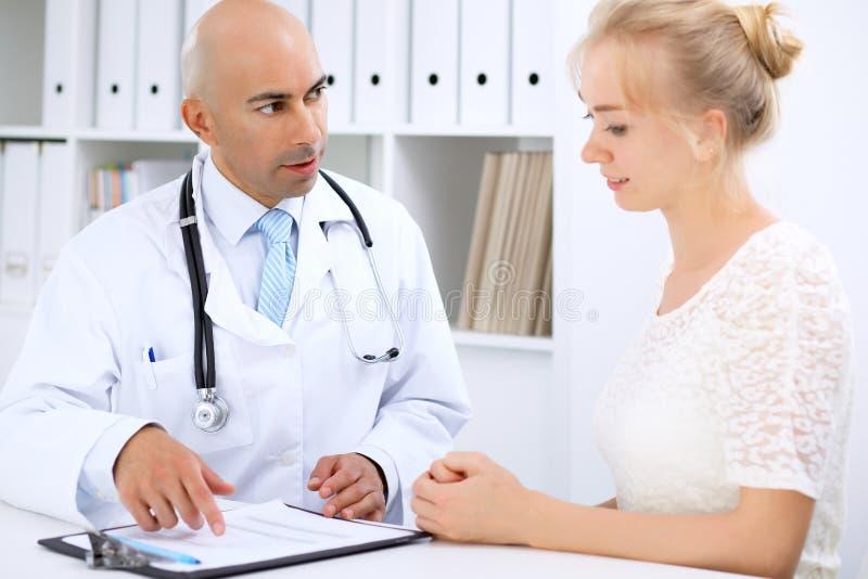Ufny łysy doktorski mężczyzna konsultuje jego żeńskiego pacjenta zdjęcie stock