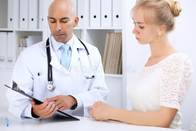 Ufny łysy doktorski mężczyzna konsultuje jego żeńskiego pacjenta obrazy royalty free
