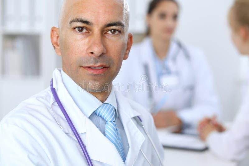 Ufny łysy doktorski mężczyzna z medycznym personelem przy szpitalem obrazy royalty free