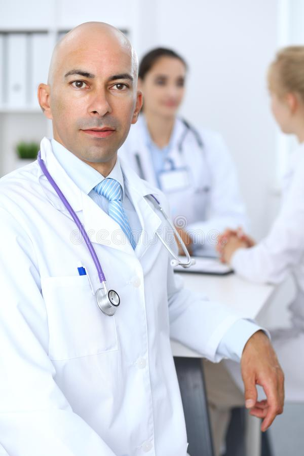 Ufny łysy doktorski mężczyzna z medycznym personelem przy szpitalem fotografia stock
