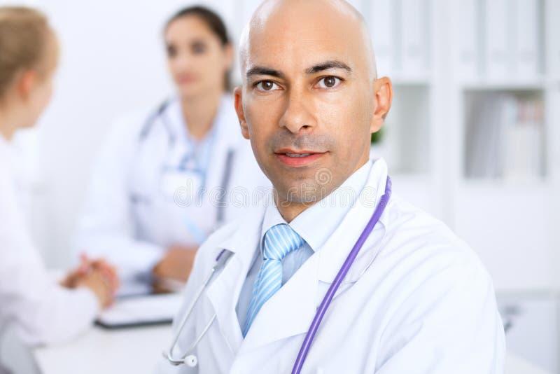 Ufny łysy doktorski mężczyzna z medycznym personelem przy szpitalem zdjęcia royalty free
