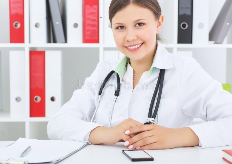 Ufny Azjatycki kobiety lekarki obsiadanie przy biurowym biurkiem i ono uśmiecha się przy kamery, opieki zdrowotnej i zapobiegania zdjęcie royalty free