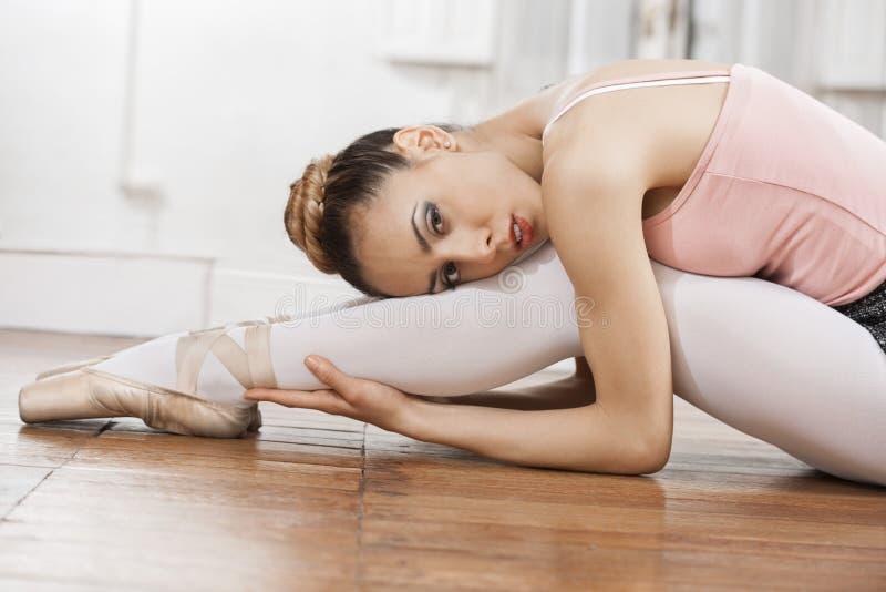 Ufny baleriny chylenie Podczas gdy Siedzący Na Drewnianej podłoga obraz royalty free