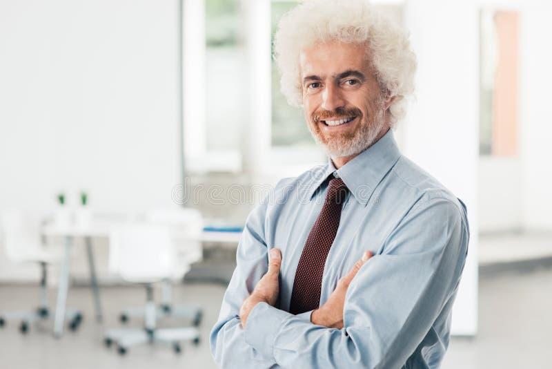 Ufny biznesmen pozuje w biurze zdjęcie stock