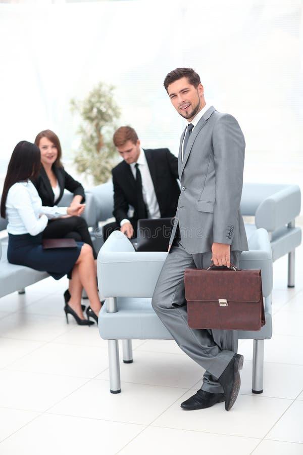Ufny biznesmen z teczki pozycją w lobby biuro zdjęcia royalty free