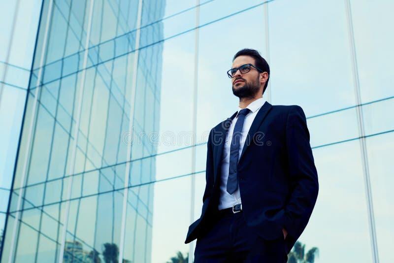 Ufny biznesowy mężczyzna stoi przeciw budynkowi biurowemu w szkłach zdjęcie royalty free
