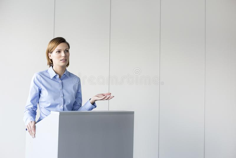 Ufny bizneswoman daje mowie przy podium przeciw ścianie w biurze obrazy royalty free