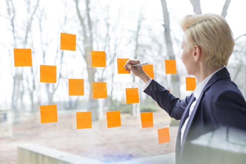 Ufny dojrzały bizneswoman pisze na pomarańczowych adhezyjnych notatkach wtykał na szklanym okno przy biurem obraz stock