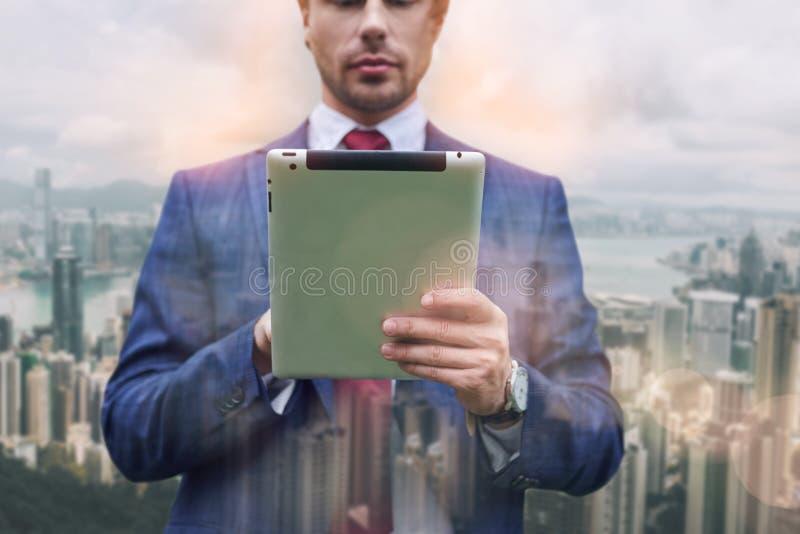 Ufny IT ekspert W górę portreta biznesmen w kostiumu używać cyfrową pastylkę podczas gdy stojący przeciw pejzażowi miejskiemu obrazy royalty free