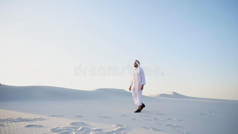 Ufny facet, arab chodzi w środku biel pustynia i cieszy się l obrazy stock