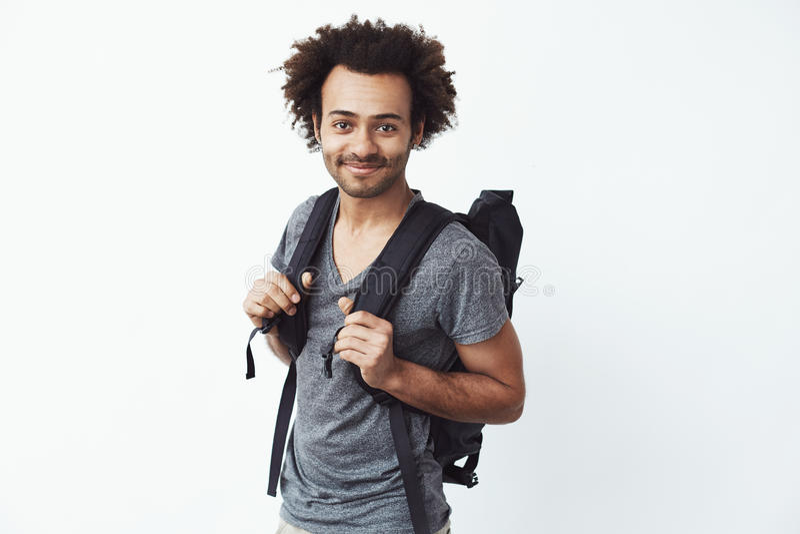 Ufny i szczęśliwy afrykański młody człowiek ono uśmiecha się z plecakiem patrzejący kamerę przygotowywającą iść hitchhiking wewną fotografia stock