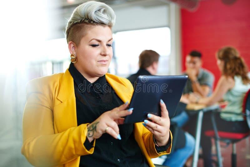 Ufny i zirytowany żeński projektant pracuje na cyfrowej pastylce w czerwonej kreatywnie powierzchni biurowa zdjęcie royalty free