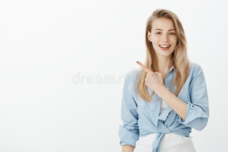 Ufny kobiecy żeński sklepowy asystent w eleganckim odziewa, podnoszący palec wskazującego i wskazujący przy górny lewy cornern obraz stock