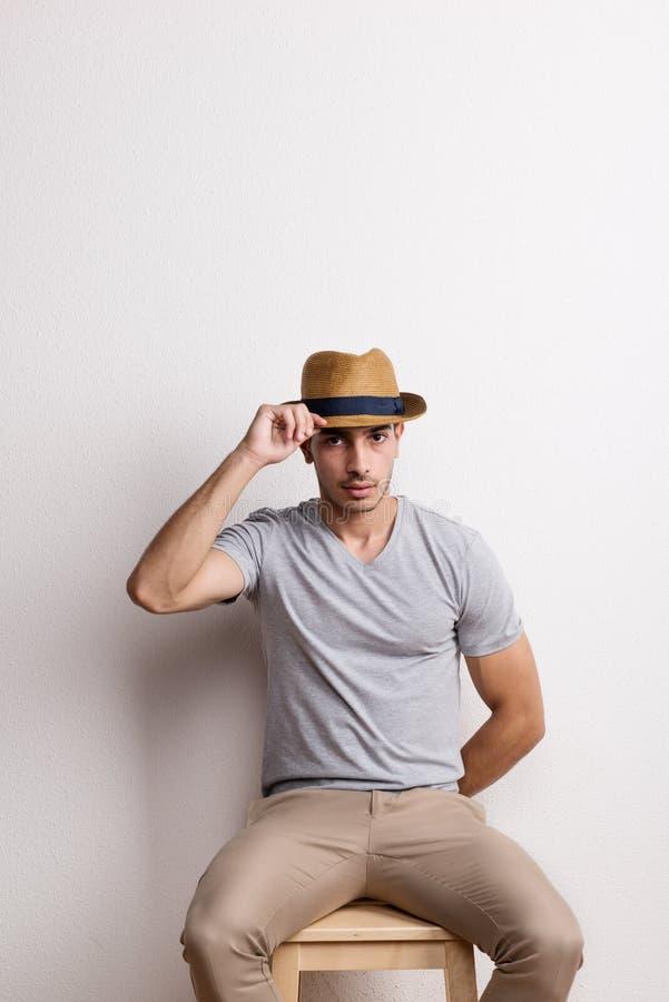 Ufny latynoski młody człowiek z kapeluszowym obsiadaniem na stolec w studiu zdjęcia royalty free