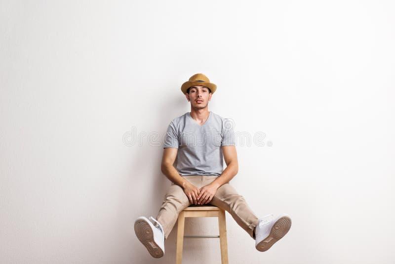 Ufny latynoski młody człowiek z kapeluszowym obsiadaniem na stolec w studiu obraz stock
