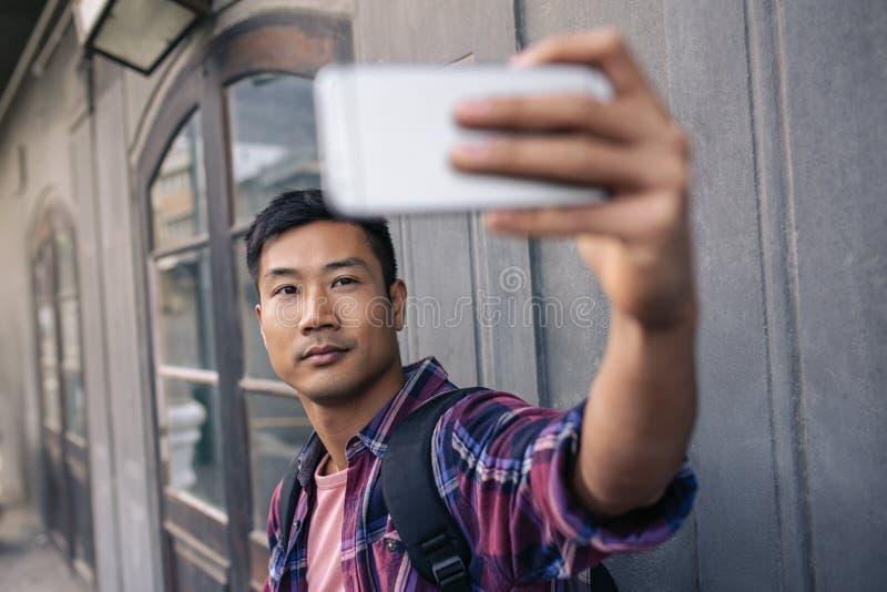 Ufny młody Azjatycki mężczyzna bierze selfies na miasto ulicie obrazy royalty free