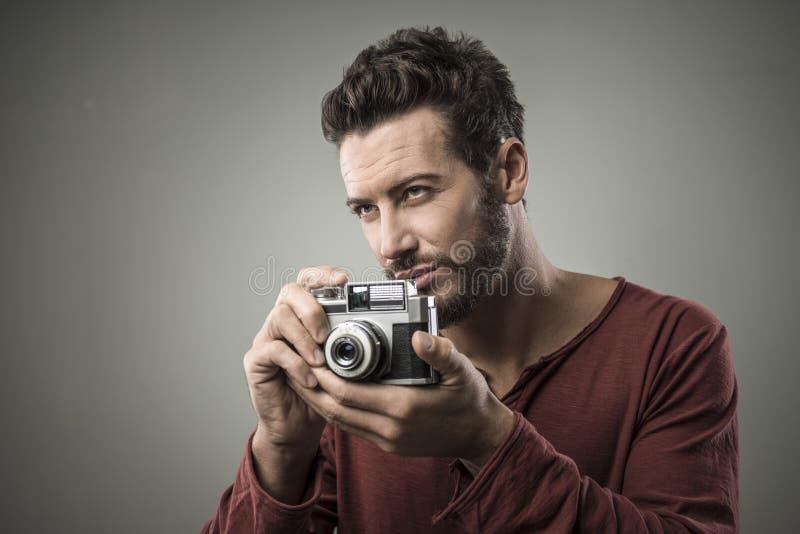 Ufny mężczyzna trzyma rocznik kamerę obraz royalty free