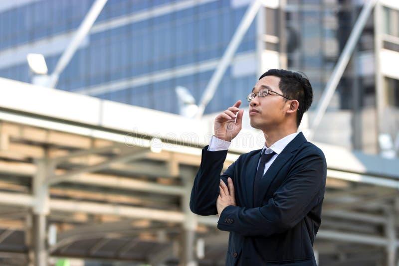 Ufny młody Azjatycki biznesowy mężczyzna w kostiumu patrzeć daleko przy outside biurem i pozycji fotografia stock