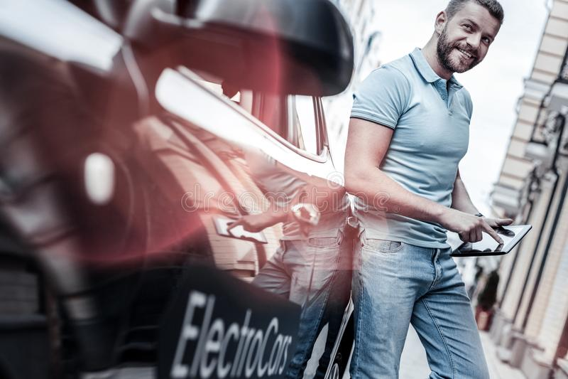 Ufny młody człowiek z pastylką opiera na nowożytnym elektrycznym samochodzie fotografia stock