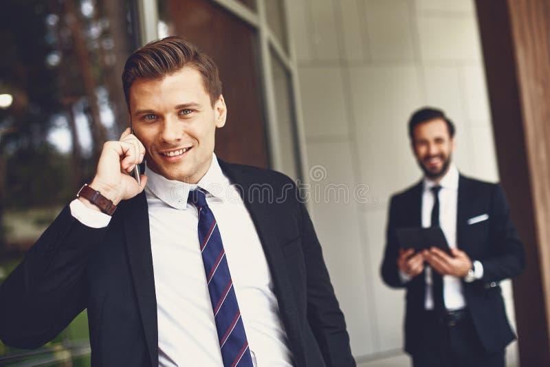 Ufny młody mężczyzna stojący z telefonem komórkowym i uśmiechający się obrazy stock