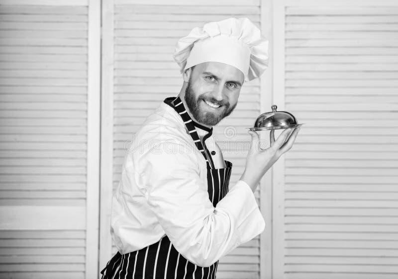 ufny m??czyzna w fartuchu i kapeluszowej chwyt tacy kucharz w restauracji, mundur brodaty m??czyzna kocha ?asowania jedzenie szef zdjęcie royalty free