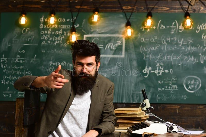 Ufny nauczyciel siedzi przy biurkiem Biznesmen z brodą w kostiumu Brodaty mężczyzna z maszyna do pisania, książkami i mikroskopem obraz stock