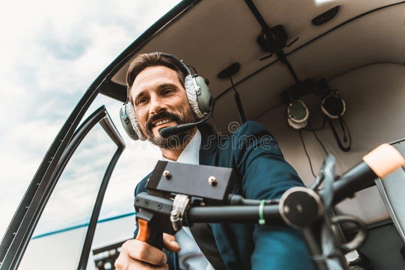 Ufny pilotowy obsiadanie w kabinie i ono uśmiecha się szczęśliwie zdjęcia stock