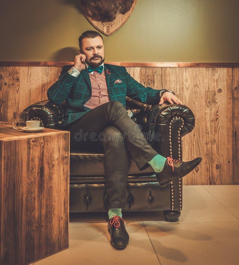 Ufny staromodny mężczyzna opowiada na telefonie komórkowym w drewnianym wnętrzu przy fryzjera męskiego sklepem obrazy stock