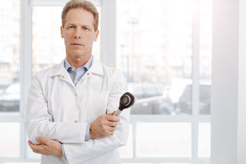 Ufny starzejący się dermatologa mienia dermatoscope przy pracą zdjęcia royalty free