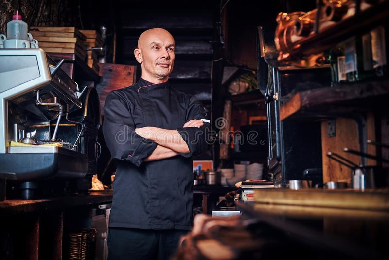 Ufny szef kuchni pozuje z jego rękami krzyżować i patrzeje daleko od w restauracyjnej kuchni obraz stock