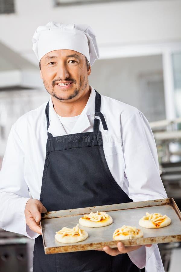 Ufny szef kuchni Trzyma Małe pizze Na pieczeniu zdjęcia royalty free