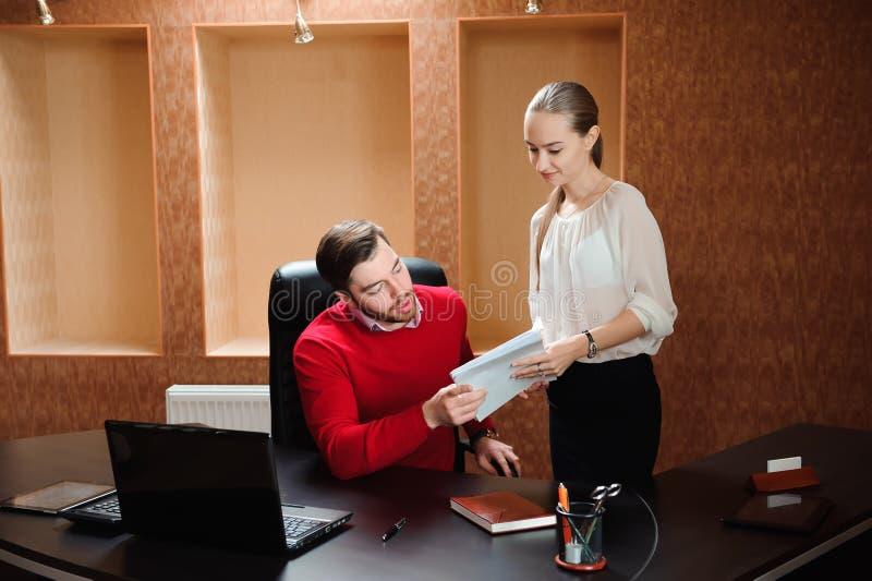 Ufny szef wyjaśnia coś sekretarka w biurze z papierem obrazy stock