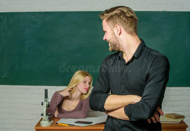 Ufny w jego wiedzie Przystojne mężczyzna pozycji ręki krzyżowali w sali lekcyjnej z nauczycielem Męski uczeń z egzaminatorem przy obraz royalty free